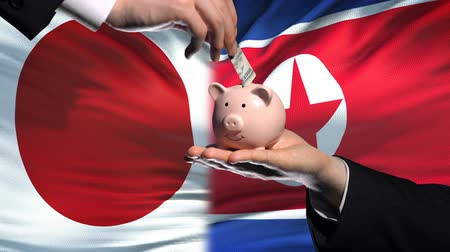 投資家 : Japan investment in North Korea hand putting money in piggybank, flag background