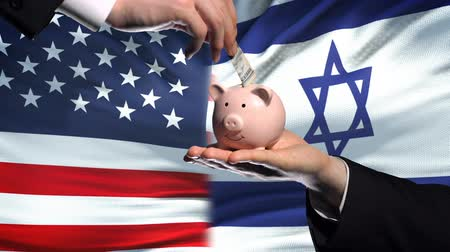 yeniden yapılanma : US investment in Israel, hand putting money in piggybank on flag background