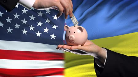 yeniden yapılanma : US investment in Ukraine, hand putting money in piggybank on flag background Stok Video
