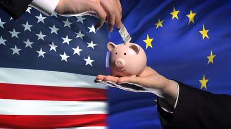 yeniden yapılanma : US investment in EU, hand putting money in piggybank on flag background, finance Stok Video