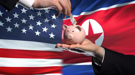 yeniden yapılanma : US investment in North Korea, hand putting money in piggybank on flag background