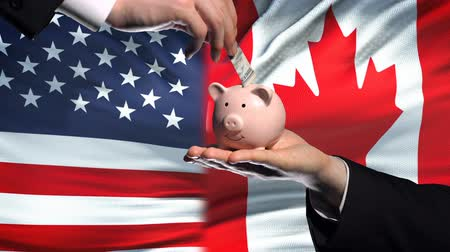 投資家 : US investment in Canada, hand putting money in piggybank on flag background