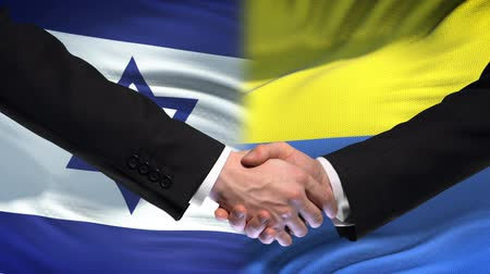 saygı : Israel and Ukraine handshake, international friendship policy, flag background