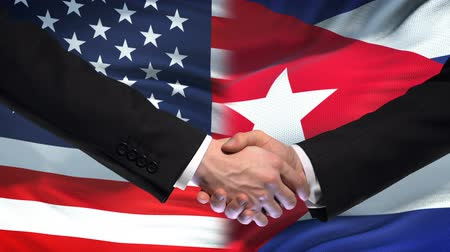 глобализация : United States and Cuba handshake, international friendship, flag background