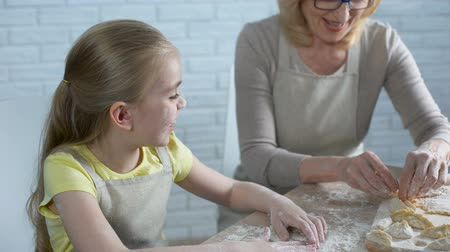 vareniki : Happy granddaughter cooking with granny, giving her high five, homemade pastry