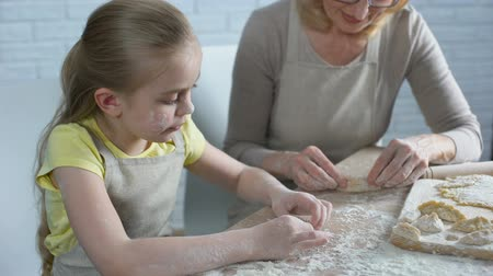 passatempo : Cute little grandchild learning to cook, helping grandmother, homemade patty Stock Footage