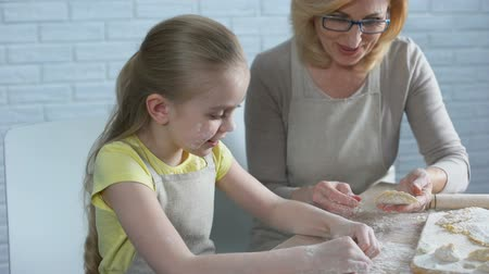 vareniki : Pretty female preschooler trying to cook pastry, helping her granny in kitchen Stock Footage