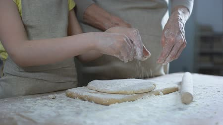 panelas : Granddaughter helping granny to roll dough, traditional recipe, homemade pastry Stock Footage