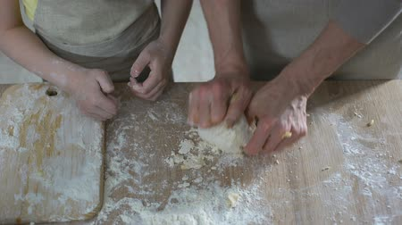 kookgerei : Grandmother teaching grandchild how to knead dough for cake, family cooking
