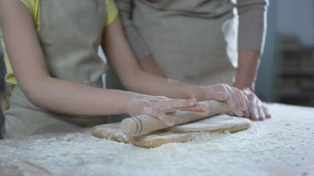 pastry ingredient : Hands of female kid rolling dough with rolling pin, helping granny to cook Stock Footage
