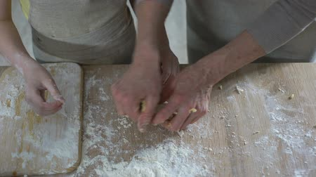 panelas : Little girl helping her grandmother to knead dough, secrets of family cooking Stock Footage