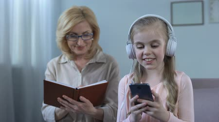 dinleme : Girl in headphones listening to music and grandma reading book, generation gap Stok Video