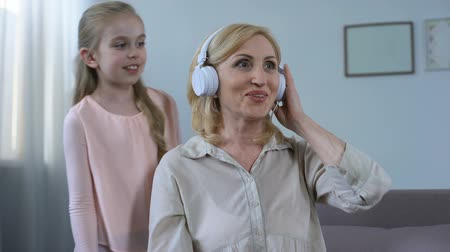 wearing earphones : Cute grandchild putting on headphones with energetic music on granny head, hobby Stock Footage