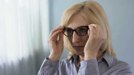 self examination : Senior businesswoman putting on eyeglasses and smiling in front of mirror health Stock Footage