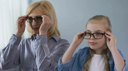 носить : Aged blond woman and her granddaughter putting on eyeglasses and smiling.