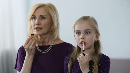 uczennica : Beautiful granny and little granddaughter applying lipstick, preparing for party