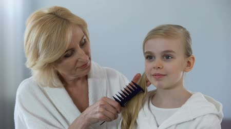 brushing : Caring grandmother combing granddaughter hair in front of mirror, family love Stock Footage