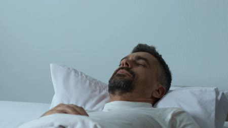restless : Anxious man waking up frightened in bed night, nightmare, troubled sleep.