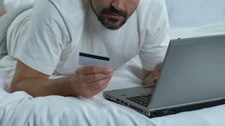 学士 : Male in bed entering card number on laptop application, online banking, shopping