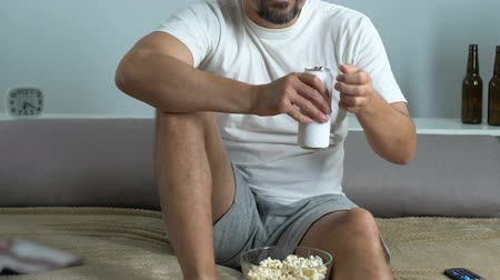 sedentary : Bachelor drinking beer, eating popcorn and watching tv.