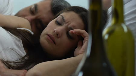 shameful : Hangover woman waking up in bed with stranger empty wine bottles on table.
