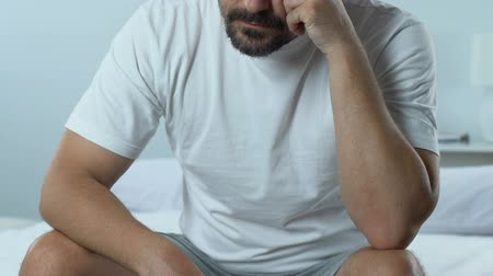 divórcio : Sad thoughtful male sitting on bed, health problem, life difficulties.