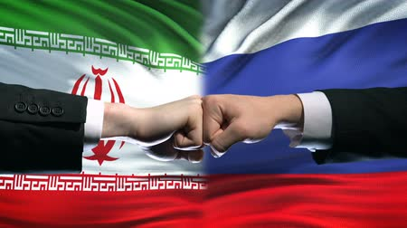 кризис : Iran vs Russia conflict, international relations, fists on flag background