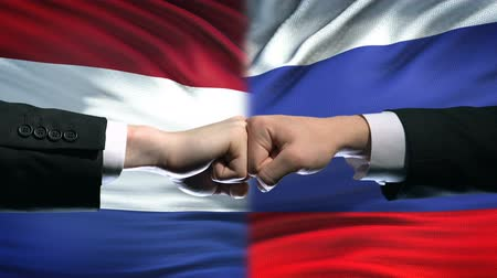 кризис : Netherlands vs Russia conflict international relations, fists on flag background Стоковые видеозаписи