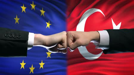 disputa : EU vs Turkey conflict, international relations crisis, fists on flag background