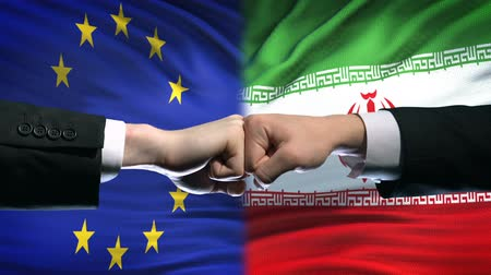 oposição : EU vs Iran conflict, international relations crisis, fists on flag background