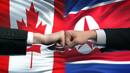 vecinos : Canada vs North Korea conflict international relations, fists on flag background Archivo de Video