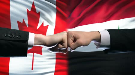 clash : Canada vs Syria conflict, international relations, fists on flag background