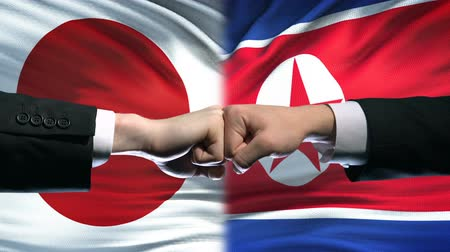 diffidenza : Japan vs North Korea conflict, international relations, fists on flag background