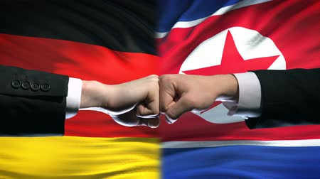 diffidenza : Germany vs North Korea conflict, fists on flag background, diplomatic crisis Filmati Stock