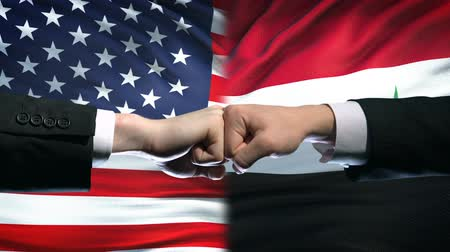 diffidenza : US vs Syria conflict, international relations crisis, fists on flag background Filmati Stock