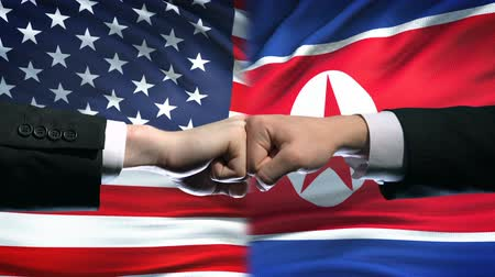 соперничество : US vs North Korea conflict, international relations, fists on flag background Стоковые видеозаписи