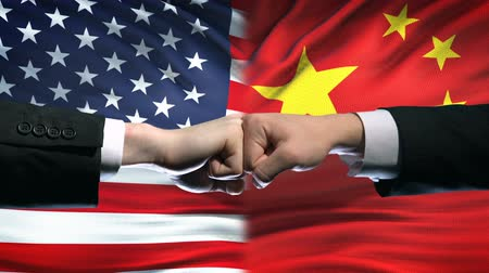 clash : US vs China conflict, international relations crisis, fists on flag background