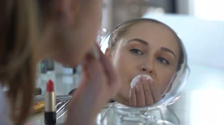cotton swab : Sad girl removing her bright makeup looking at reflection, unsuccessful date