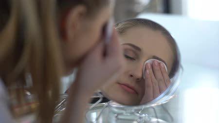 化粧品 : Girl easily removing make-up from eyes with new lotion, testing of removers 動画素材