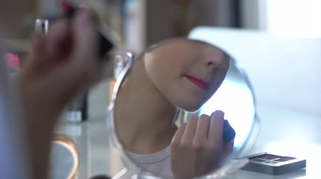 kadınlık : Lady putting seductive evening makeup smiling to her reflection in mirror