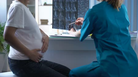 complaints : Traumatologist considering mri of back of pregnant woman who complaints of pain Stock Footage