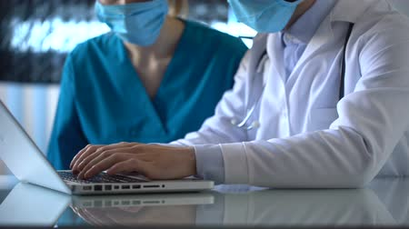 estagiário : Laboratory workers checking medical test results on laptop, discussing illness