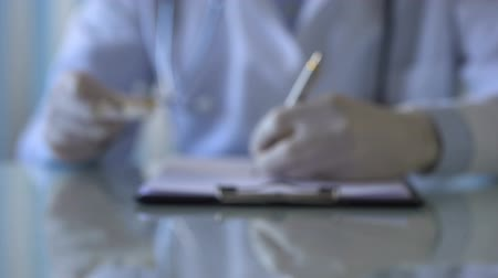 prescribe : Physician writing prescription and giving colored pills to patient, close-up Stock Footage
