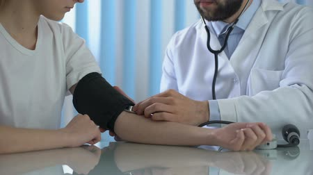 hypertension : Male therapist measuring blood pressure of young woman, health care, medicine