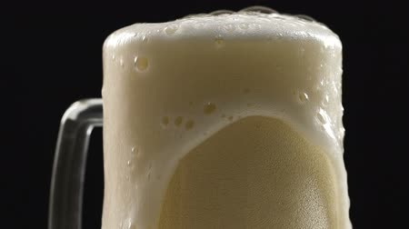 ale : Beer pouring in glass, white frothy foam flowing over, craft brewery.