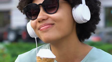laktóz : Carefree mixed-race girl listening to favorite song, eating ice-cream, happiness Stock mozgókép