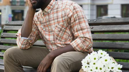 smutek : Frustrated afro-american man sitting on bench after breakup with girlfriend Wideo