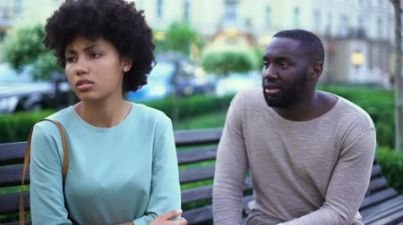 jealous : Young man talking to offended girlfriend on bench, jealous woman, break up
