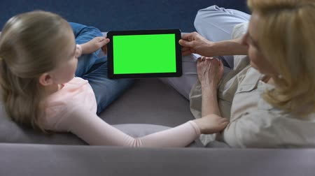 unokája : Grandmother and little female grandkid holding tablet with green screen, apps
