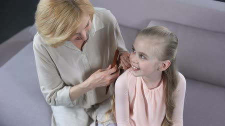 parentes : Caring mature mother combing daughter blond hair.